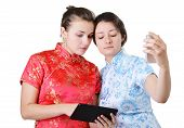 stock photo of gizmo  - Two Caucasian young women are standing and using a mobile phone and a pad - JPG
