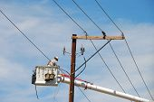 stock photo of lineman  - Power company lineman working on the instalation of power lines using a boom truck - JPG