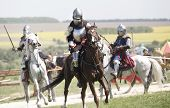 stock photo of pageant  - Medieval knights in battle background with horse - JPG