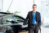 stock photo of showrooms  - dealer stands near a new car in the showroom - JPG