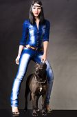 stock photo of friendship belt  - Beautiful woman in jeans clothes  standing next to a dog - JPG