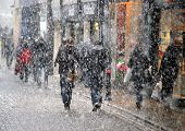 picture of street-walker  - business shoppers people weather snow winter seasons falling walkers snowfall pedestrians high street urban trade color colorful movement concepts conceptual busy - JPG