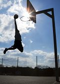 image of slam  - Silhouette of a man about to slam dunk with lens flare - JPG
