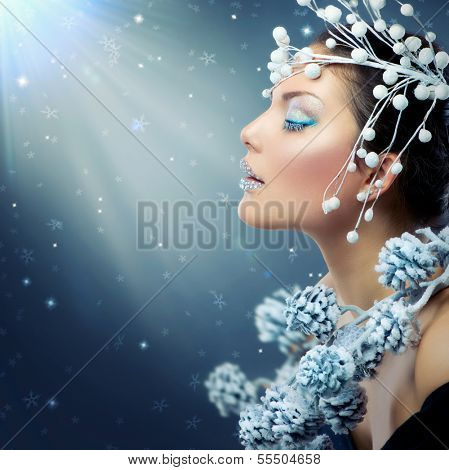 Winter Beauty Woman. Christmas Model Girl Makeup. Holiday Make-up. Snow Queen High Fashion Portrait over Blue Snow Background. Eyeshadows, False Eyelashes and Crystals on the Lips.