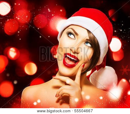 Christmas Woman. Beauty Model Girl in Santa Hat over Glowing Holiday red Background. Funny Laughing Surprised Woman Portrait. Open Mouth. True Emotions. Red Lips and Manicure. Beautiful Makeup.