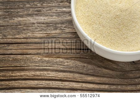 semolina wheat flour - a white ceramic bowl on a grained wood