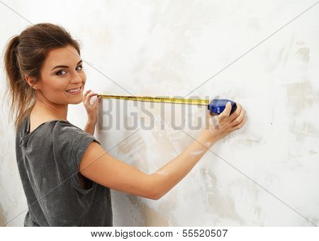 Young beautiful brunette woman measuring spacing on a wall with roulette