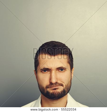 portrait of displeased man with empty copyspace above his head