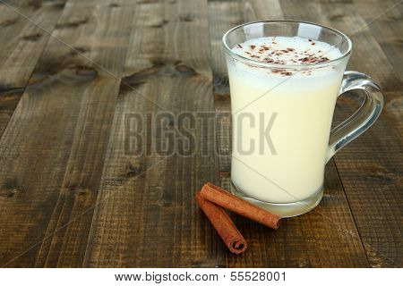 Cup of eggnog with cinnamon on wooden background