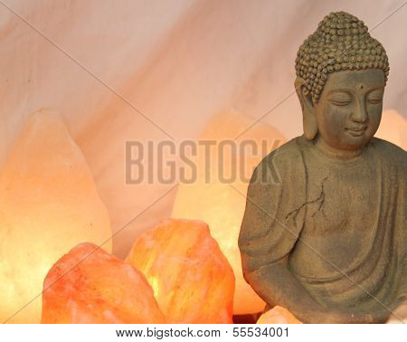 statuette of Buddha in prayer with salt lamps lit during the meditation of the disciples