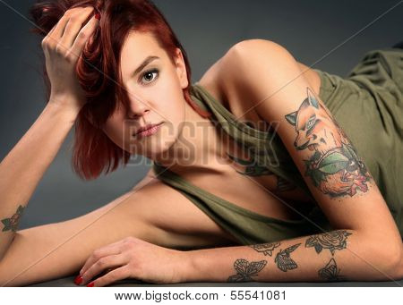 Young tattooed girl on dark background