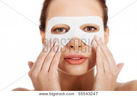 Beautiful woman with collagen mask on eyes. Isolated on white.
