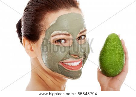 Beautiful spa woman in facial mask and avocado. Isolated on white.