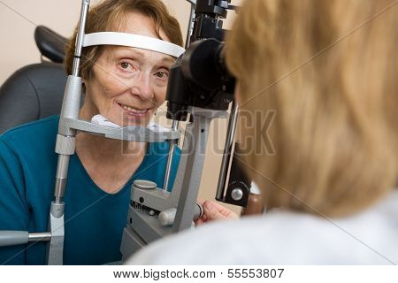 Portrait of senior woman having eye test with slit lamp in store