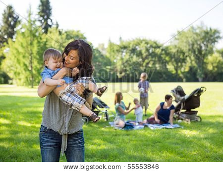 Young woman carrying baby boy with friends and children in background at park