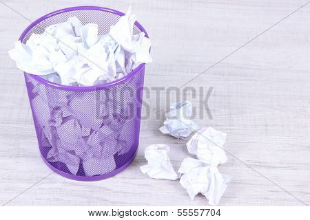 Recycle bin filled with crumpled papers, on floor