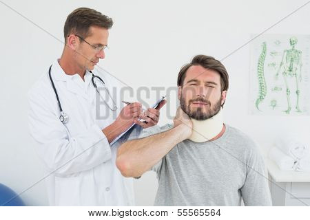 Male doctor examining a patient's sprained neck in the medical office