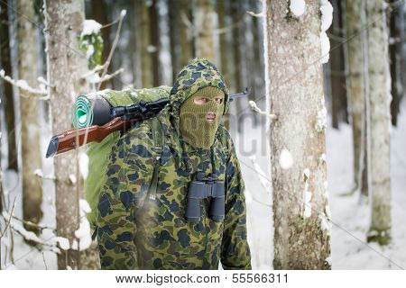 Hunter with optical rifle and binoculars in the backwoods