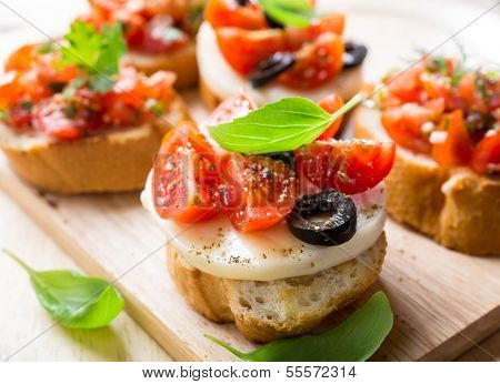 Italian Appetizer Bruschetta with roasted tomatoes, mozzarella cheese, black olives and herbs
