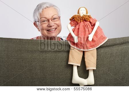 Granny presenting a puppet show, smiling.