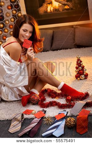 Sexy woman in silk gown and christmas socks arranging christmas gifts, tie with name tag for men.