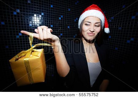 Portrait of young businesswoman in Santa cap holding Chistmas gift and looking at it with sneer