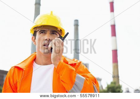 Male construction worker wearing reflective workwear communicating on two way radio at site