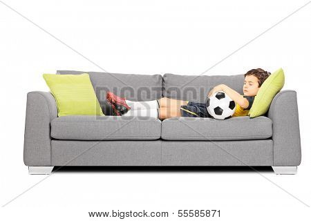 Boy in sportswear with a soccer ball sleeping on a modern sofa isolated on white background