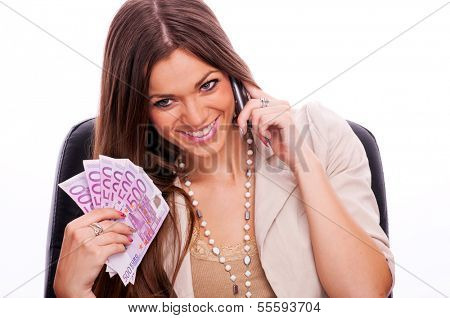 Young business woman sitting in the chair, talking on the mobile phone and holding european money - isolated on white