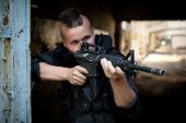 foto of m4  - Aiming man with M4 rifle on the ruined building background - JPG