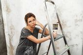 Disgruntled young brunette woman with ladder and painting brush poster