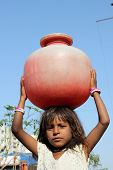 stock photo of drinking water  - A poor Indian girl carrying water to her home in a red plastic pot due to scarcity of drinking water to poor people in India - JPG