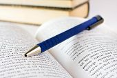 stock photo of bookworm  - Close up of opened book pages with pen