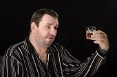 pic of boose  - Mature guy rises glass of brandy on black background - JPG