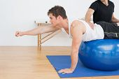 foto of physical therapist  - Physical therapist assisting young man with yoga ball in the gym at hospital - JPG