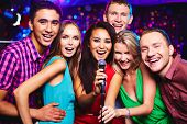 foto of karaoke  - Portrait of happy girls and guys singing in microphone in the karaoke bar  - JPG
