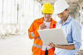 stock photo of headgear  - Male architects using laptop at construction site - JPG