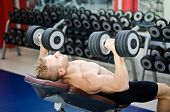 stock photo of shoulder muscle  - Muscular young man shirtless lifting dumbbells training pecs on gym bench - JPG