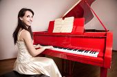 picture of grand piano  - Happy woman in dress playing the red grand piano smiling and looking at camera - JPG