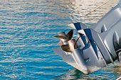 picture of outboard  - a boat engine propellers over blue water - JPG