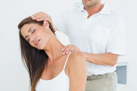 stock photo of chiropractor  - Male chiropractor doing neck adjustment in the medical office - JPG