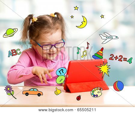 Child sitting with tablet computer and learning or playing with great interest
