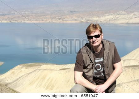 Man Poses On Toktogul Reservoir Background