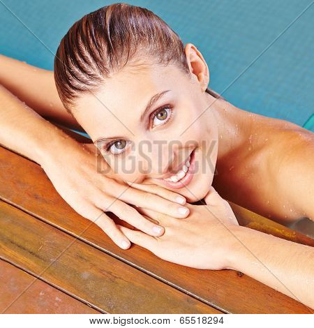 Face of young attractive woman on edge of swimming pool in summer