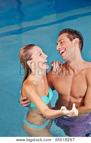 Laughing couple together in a swimming pool in a hotel