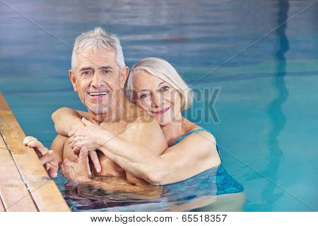 Happy couple senior people bathing in a swimming pool