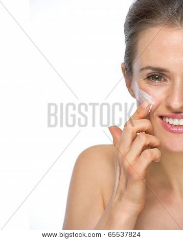 Closeup On Happy Young Woman Applying Creme