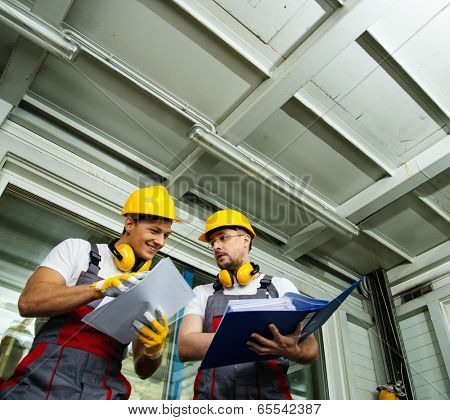 Two workers  in a factory control room reading documentation