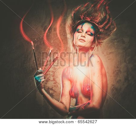 Young woman muse with creative body art and hairdo with paint brushes