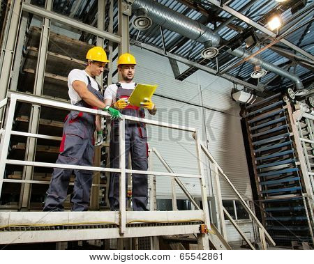Two workers in safety hats on a factory reading plan